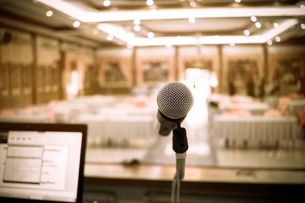 Microfoni e notebook computer sul palco davanti nella sala per seminari