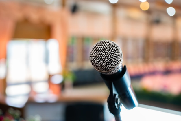 Microfoni su astratto sfocato di discorso nella sala seminari o conferenza frontale