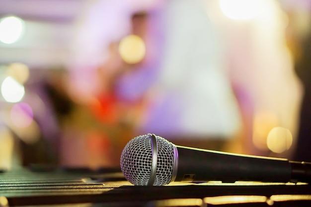 Microfono del primo piano sulla tabella nera in un partito e nella priorità bassa confusa.