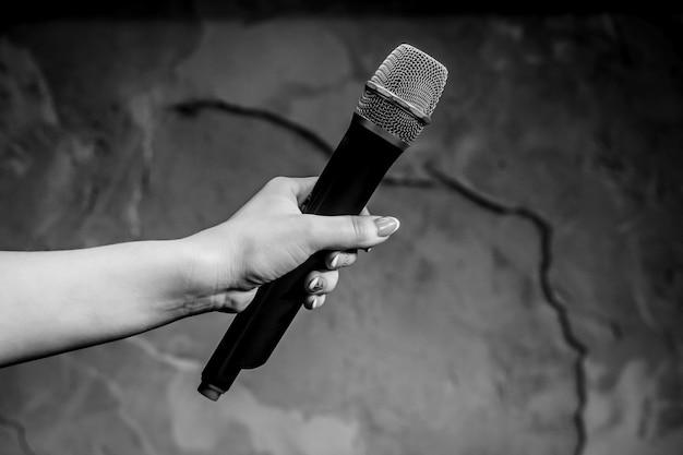 Microfono della holding della donna su priorità bassa grigia, primo piano. foto bianca e nera