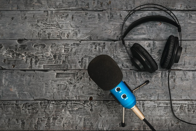 Microfono e cuffie su un tavolo di legno nero.