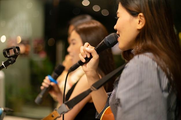 Microfono e gruppo irriconoscibile di cantante femminile sul palco durante la notte