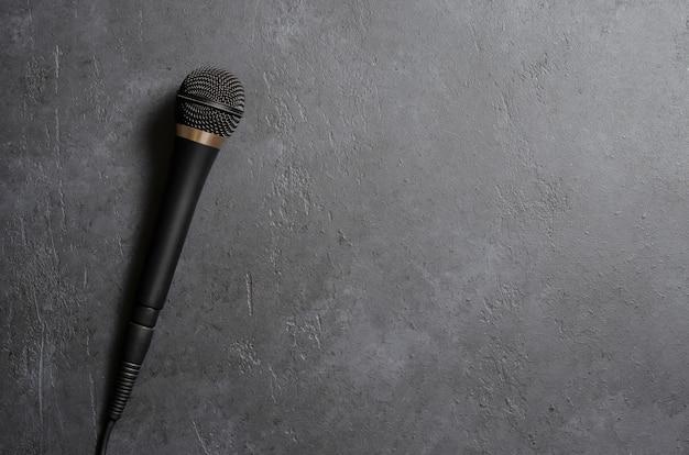Microfono nero su un tavolo di cemento scuro. attrezzature per voce o interviste o relazioni. copia spazio