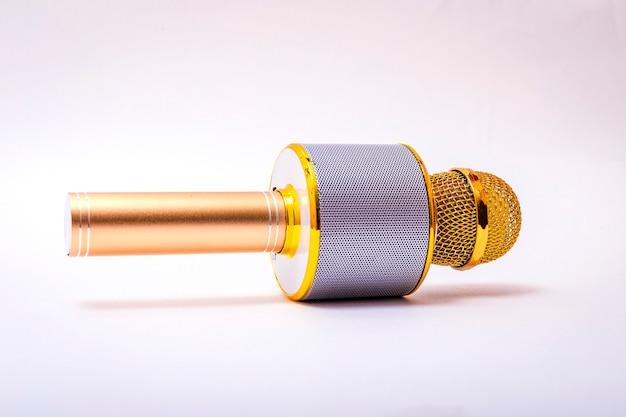 Microfono senza fili dorato isolato sopra fondo bianco.