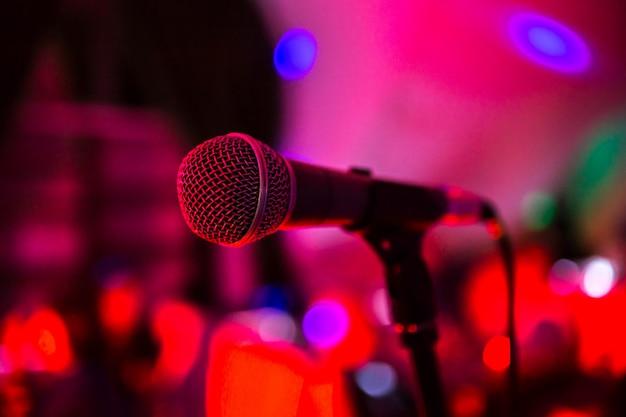 Microfono si erge sul palco in un locale notturno. luminosa