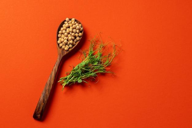 Microgreens e ceci in cucchiaio di legno su sfondo arancione scuro