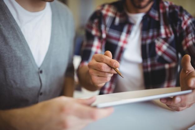 Midsection degli uomini d'affari che utilizzano compressa digitale nell'ufficio