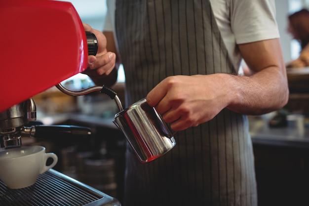 Midsection del barista che usando macchinetta del caffè espresso al caffè