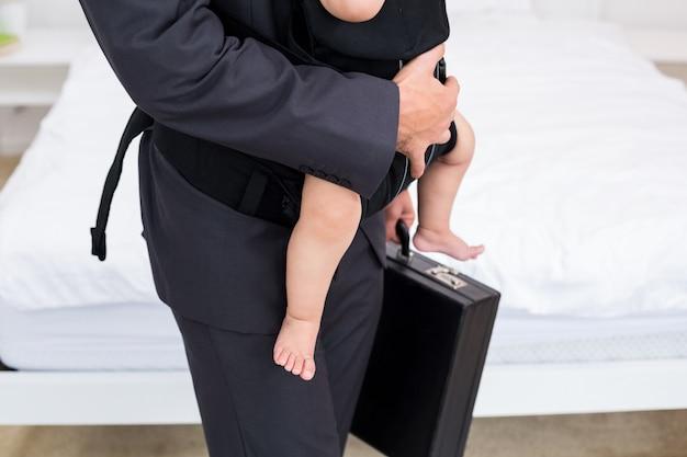 Midsection del padre che trasporta il bambino con valigetta