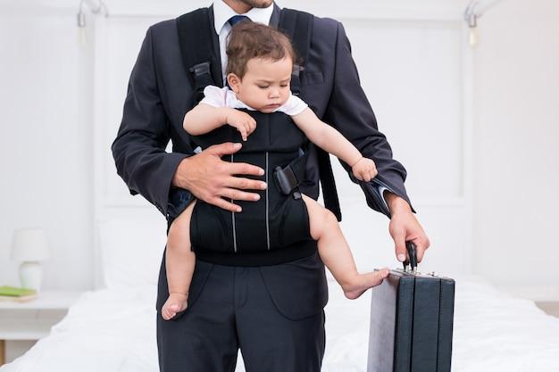 Midsection del padre che trasporta il bambino mentre si tiene valigetta