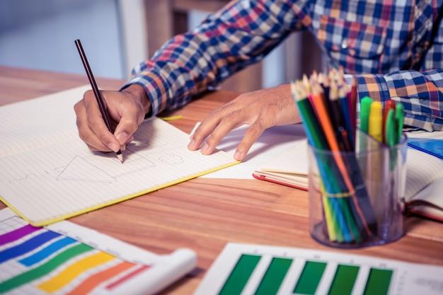 Midsection del progettista che attinge libro allo scrittorio in ufficio creativo