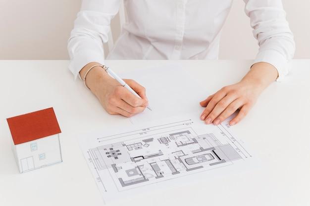 Midsection della donna che lavora al modello della casa allo scrittorio in ufficio