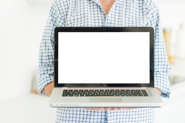 Midsection della donna che mostra computer portatile con lo schermo bianco
