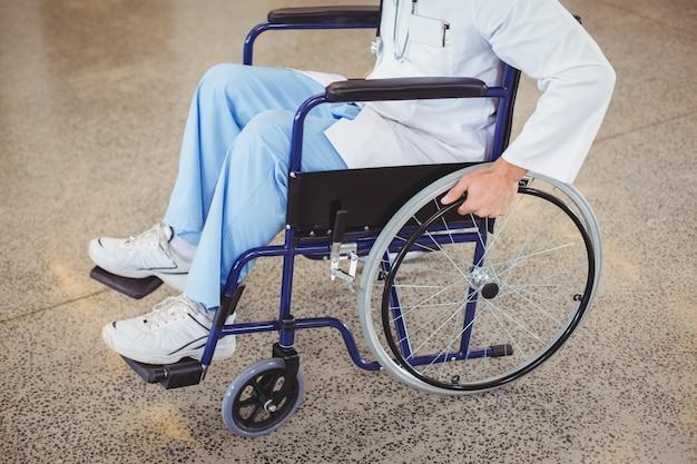 Midsection di medico che si siede sulla sedia a rotelle