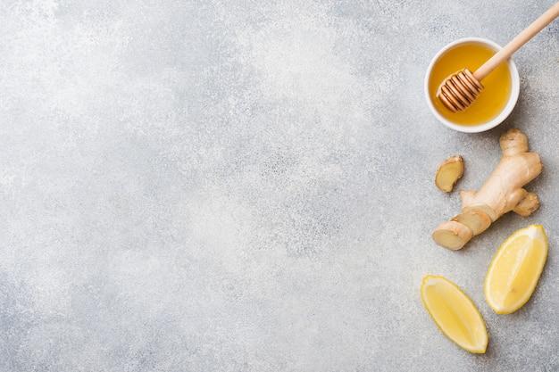 Miele al limone e radice di zenzero sulla superficie grigia