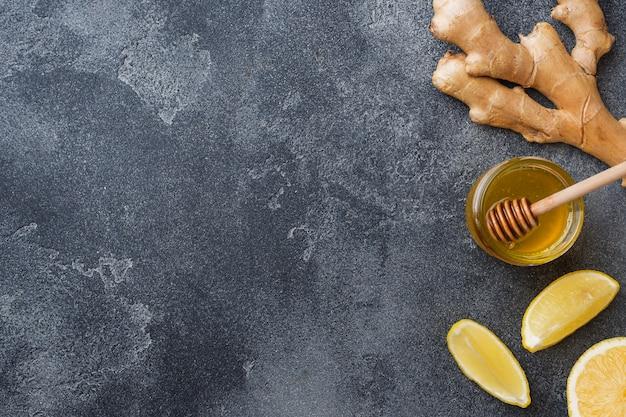 Miele al limone e radice di zenzero sulla superficie grigio scuro