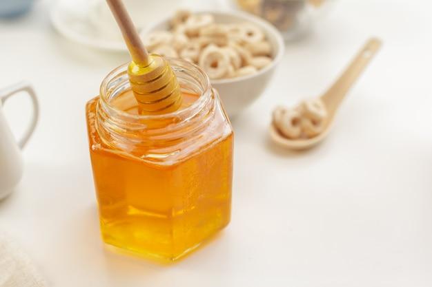 Miele aromatico di versamento nel barattolo, primo piano