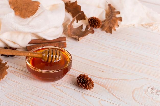 Miele, bastoncino, barattolo, sciarpa, foglie secche. foto dolce rustica di autunno, fondo di legno bianco, copyspace.
