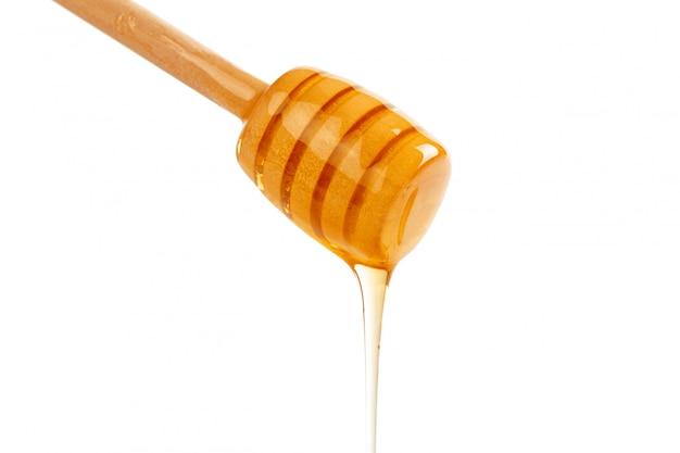 Miele con drizzler di legno isolato
