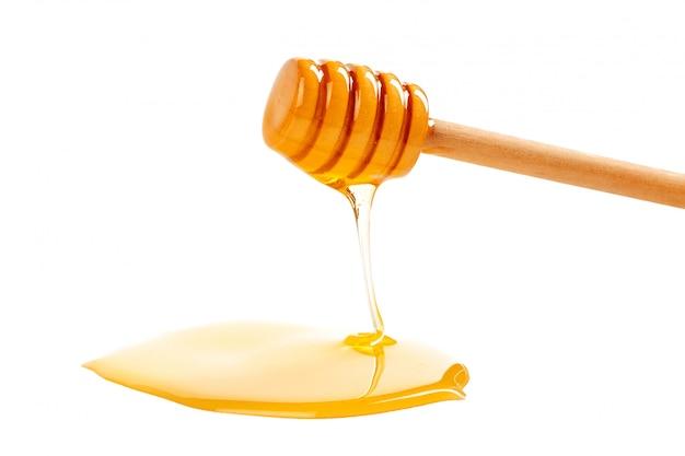 Miele con drizzler in legno isolato su bianco