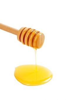 Miele con drizzler in legno isolato