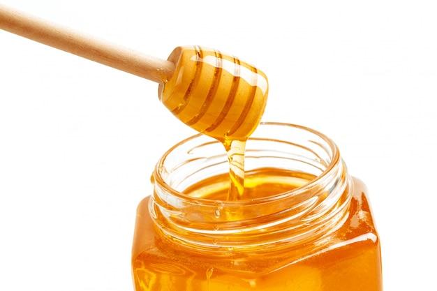 Miele con il bastone di legno isolato su bianco