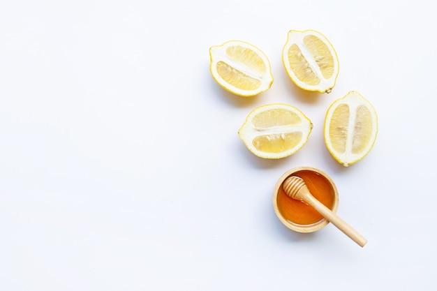 Miele con limone su sfondo bianco.