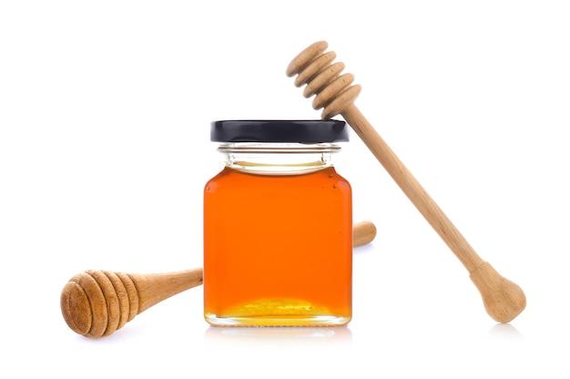 Miele con mestolo in legno miele sul barattolo