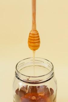 Miele del primo piano che versa nel barattolo