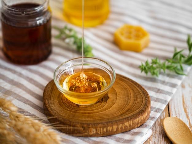 Miele delizioso che versa in ciotola