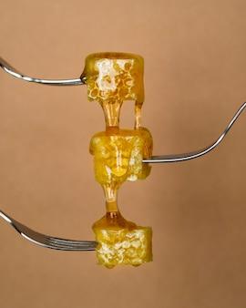 Miele delizioso che versa sui cucchiai