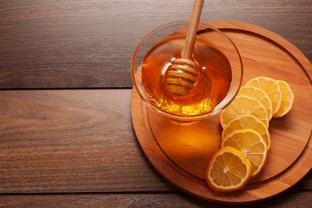 Miele delizioso del primo piano con le fette del limone