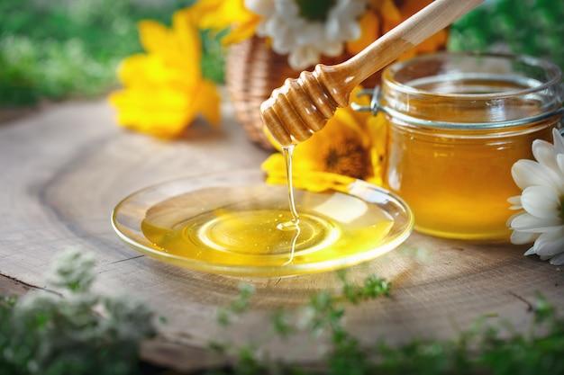 Miele di fiori freschi su un tavolo di legno. messa a fuoco selettiva