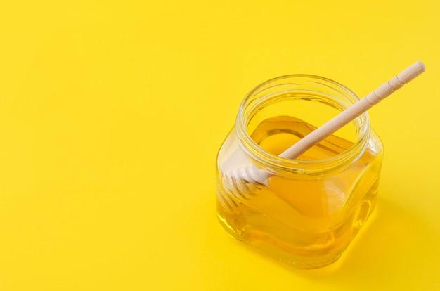 Miele di fiori liquidi in vaso di vetro con cucchiaio di miele in legno.