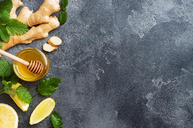 Miele di limone e zenzero radice di menta su sfondo grigio scuro con spazio di copia. ingredienti per una bevanda vitaminica tonica.