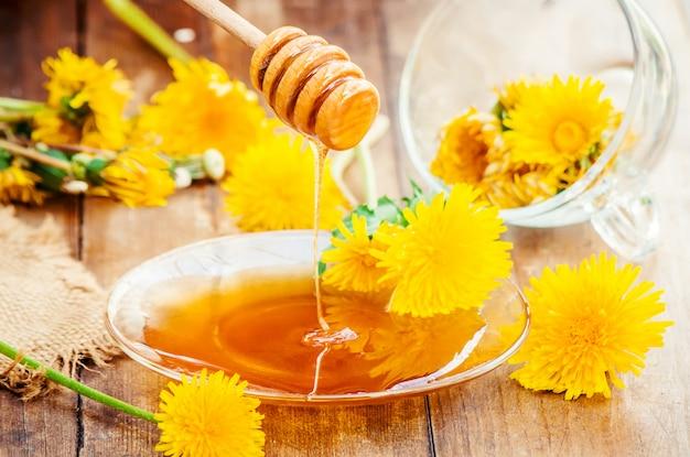Miele di tarassaco e una tazza di tè. messa a fuoco selettiva