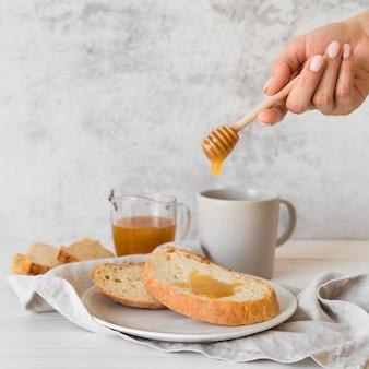Miele di versamento della mano di vista frontale sopra la fetta di pane
