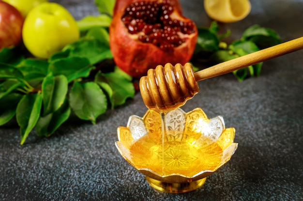 Miele dolce naturale con bastoncino di legno e melograno.
