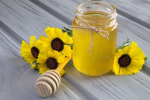 Miele e fiori sul legno grigio