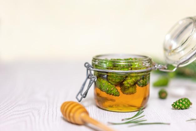 Miele e giovani pigne verdi in un barattolo di vetro aperto su una tavola di legno leggera.