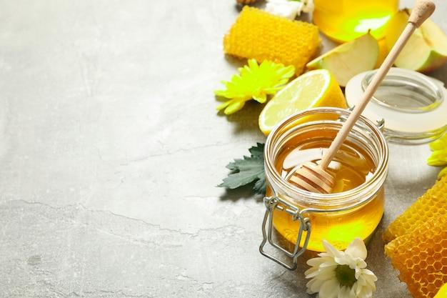 Miele, fiori e frutti su sfondo grigio, copia spazio
