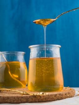 Miele fresco che gocciola in vaso di vetro sui sottobicchieri del sughero contro fondo blu