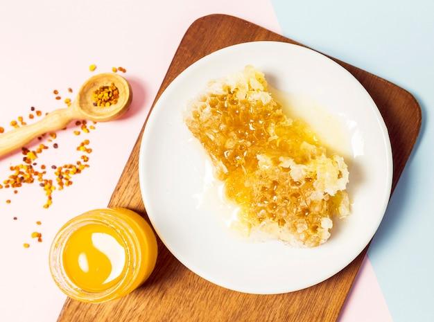 Miele fresco e nido d'ape organico con polline d'api su sfondo bianco