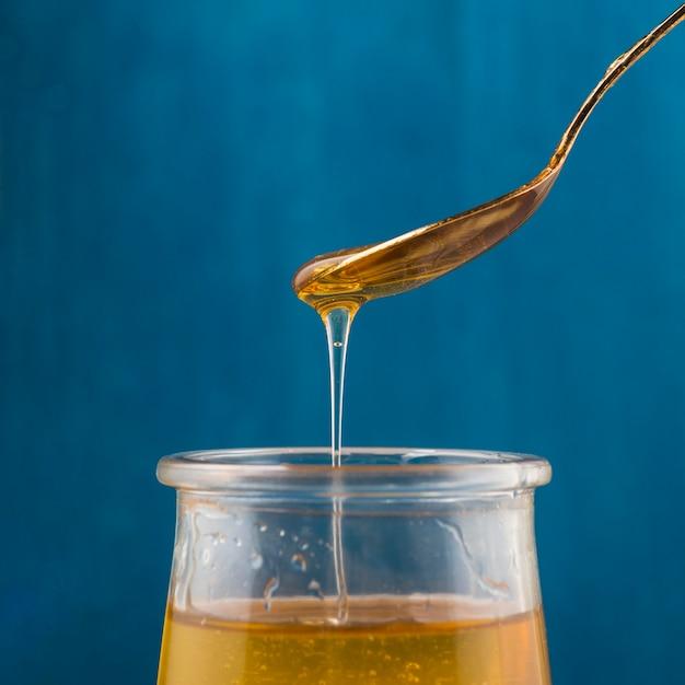 Miele gocciolante dal cucchiaio in vaso di vetro su sfondo blu