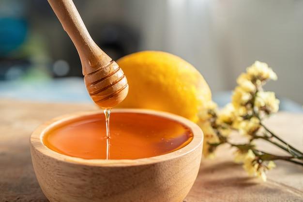 Miele grosso che si intinge con un cucchiaio di legno da una ciotola di legno