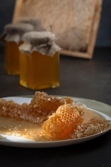 Miele in barattoli di vetro e favi sul tavolo.