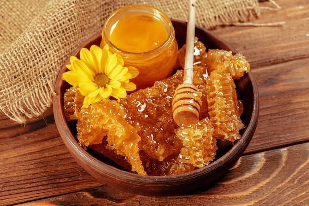 Miele in barattolo con merlo acquaiolo del miele su legno d'epoca
