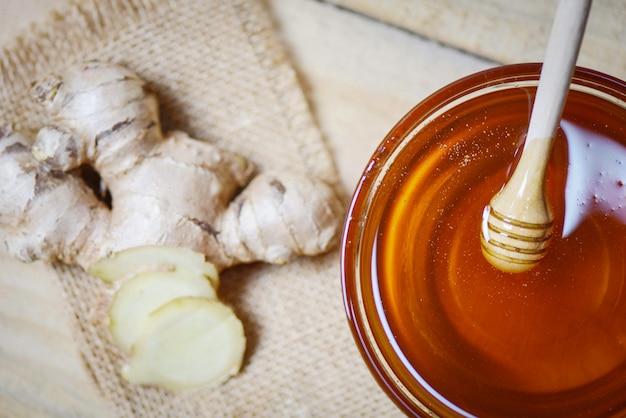 Miele in barattolo con mestolo di miele e zenzero sul sacco in legno