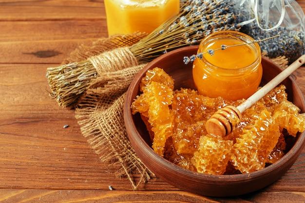 Miele in barattolo con mestolo di miele su legno vintage