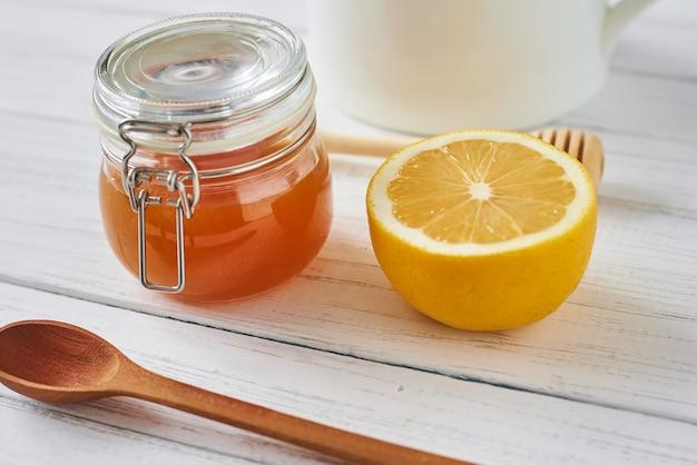 Miele in barattolo di vetro e limone sulla fine bianca della priorità bassa in su
